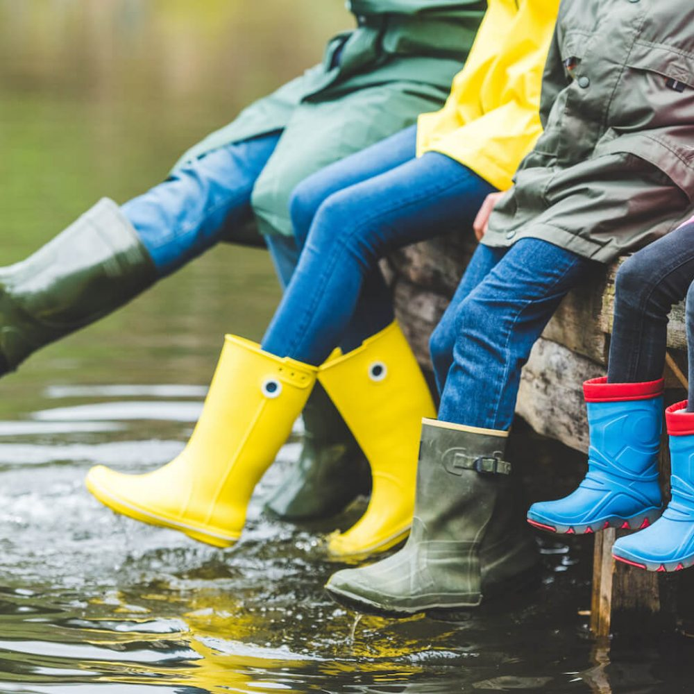partial-view-of-family-in-rubber-boots-sitting-on--B8NXECJ